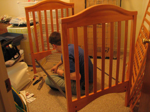 Charlie sits imprisoned while assembling the crib